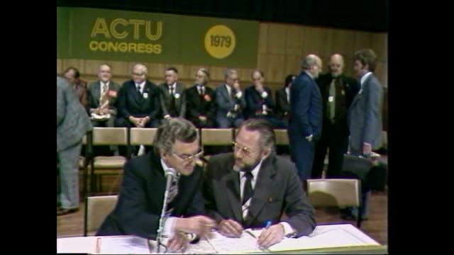 ACTU President Bob Hawke walks into hall / ACTU Congress 1979 logo on wall / vs delegates / Hawke at table in discussion / delegates incl Barrie...