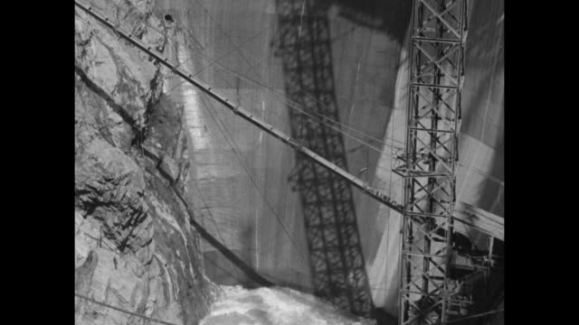 cranes pouring concrete train car full of dirt coming up funicular men ride piece of metal suspended from cable via pulley above bridge / Note exact...