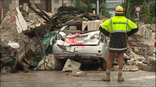 Damage near Cathedral Square with entrance to street framed with piles of fallen bricks and crushed car crane and remains of Christ Church Cathedral...