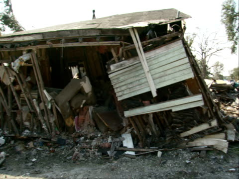 Damaged crushed pickup truck in front of damaged home house w/ collapsed roof missing walls debris fallen trees LA natural disasters levees