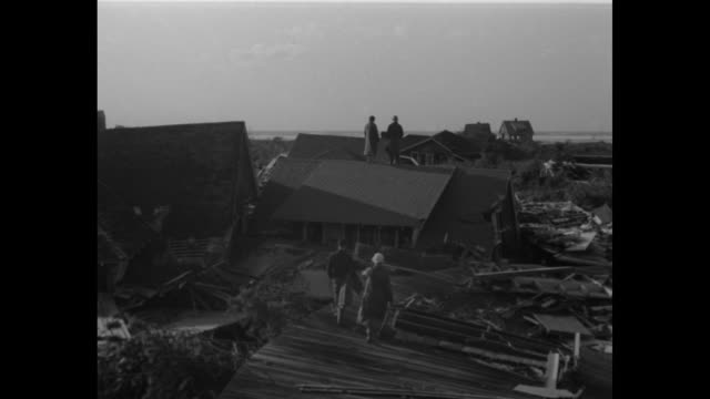 WS damaged pier in Westhampton Long Island with damaged house in background / the same house partially wrecked stands with its verandah and upper...