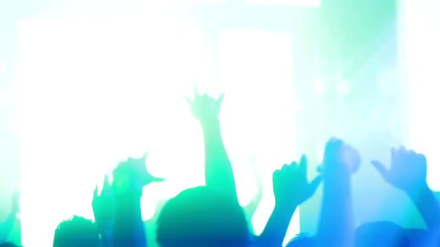 Danza folla di persone con le mani in discoteca
