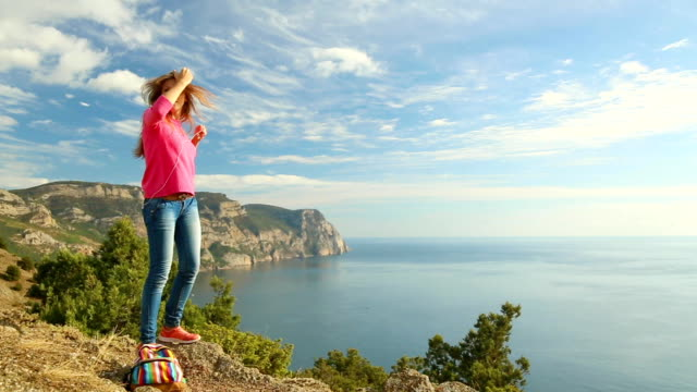 dancing girl with a smartphone on the mountain coast