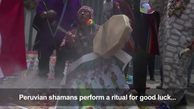 Dancing on a photo of the New Zealand team with a live snake Peruvian shamans perform a ritual outside of the National Stadium in Lima aiming to...
