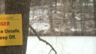 MS PAN Danger Ice Unsafe Keep Off sign posted on tree with frozen lake at high park / Toronto, Ontario, Canada