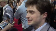 Daniel Radcliffe standing on red carpet outside Ziegfeld Theater talking to press MTV reporter