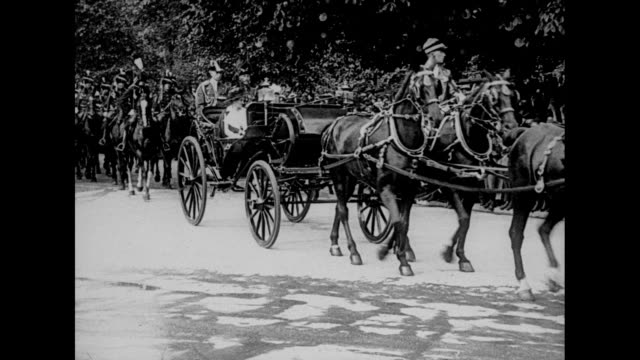 Danish King Christian X and Netherlands Queen Wilhelmina in horsedrawn carriage coming down street / Danish Queen Alexandrine and Netherlands Prince...