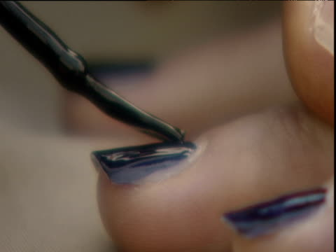 Dark blue nail polish being painted onto fingernails