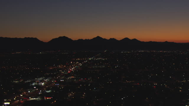 WS AERIAL Dark city and sun light on horizon behind mountains / Phoenix, Arizona, United States