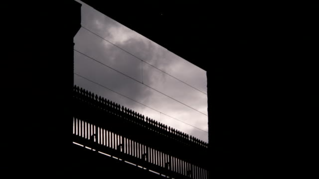 Dark clouds move across the sky above a viaduct. Available in HD.