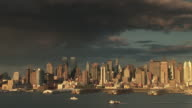 Dark clouds over the skyline of the upper west side in manhattan at sunset showing boats passing on the hudson river