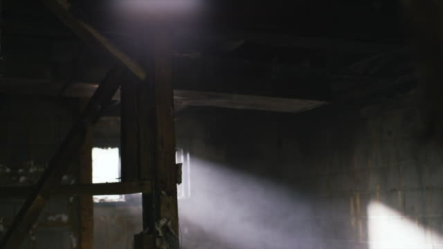 Dark, eerie scene of a burned out basement, smoke drifts out an open window.