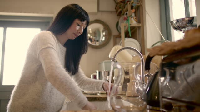 A dark haired woman washing dishes in a kitchen