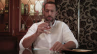 dark short haired tanned man with trimmed beard in white shirt in his 30s sits in a cigar lounge with a glass of scotch whiskey - he grabs the glass and takes a sip of his alcoholic drink - ashtray with cigar out of focus in foreground