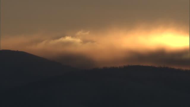 Dark storm clouds drift over hills at sunrise, Yellowstone, USA