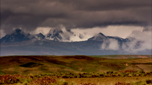 Dark storm clouds hang over grasslands near snow-covered mountain peaks. Available in HD.