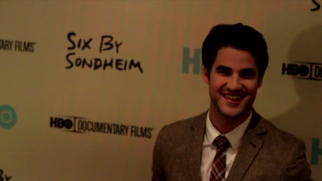 Darren Criss posing for paparazzi on the red carpet at the Museum of Modern Art