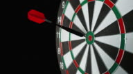 SLO MO dart with red flight hitting the bulls eye
