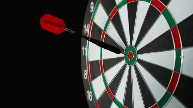 SLO MO dart with red flight hitting the bulls eye