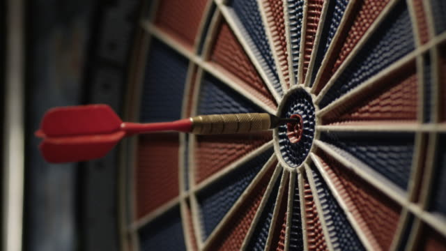 Darts striking a dartboard. Slow motion.
