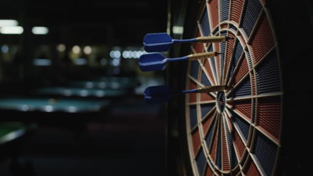 Darts striking a dartboard. Slow motion.
