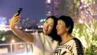Daughter and mother take a selfie with mobile phone