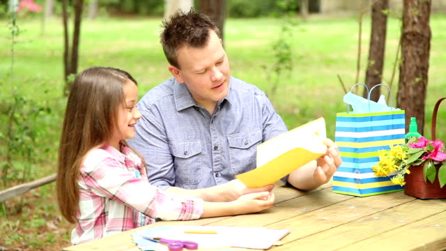 Daughter gives dad handmade Father's Day card. Outdoors. Child, parent.