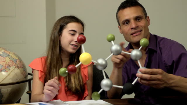 Daughter Shows Father her Science Project of a Molecule