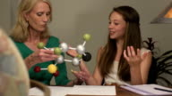 Daughter Shows Mother her Science Project of a Molecule CU
