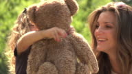 MS SLO MO Daughter smiles she receives teddy bear from mother  / New York, New York, United States