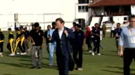 David Cameron press conference / David Cameron plays cricket Cameron and Muralitharan walking on pitch surrounded by young cricketers / young...