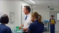 David Cameron reading a hospital notice board accompanied by two nurses