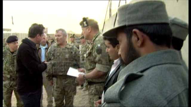 David Cameron visit to Camp Bastion EXT 'Helmand Police Training Centre' sign at entrance gates/ various of David Cameron meeting group of Afghan...