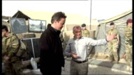 David Cameron visit to Camp Bastion Various of David Cameron being shown sacks of aid including tins of food fertilizer and cricket bat Various shots...