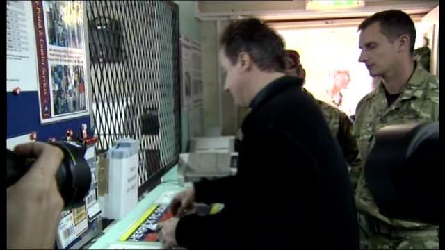 David Cameron visit to Camp Bastion Various shots of David Cameron meeting British troops working in military post office/ David Cameron writing...