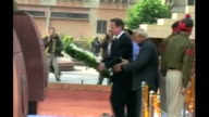 Wreath laying INDIA Amritsar EXT David Cameron MP along with others / side view of Cameron laying wreath at memorial / Cameron standing with head...