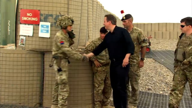 David Cameron visits British troops in Helmand Province on Armed Forces Day GVs Chinook helicopter landing and Cameron getting off and walking along...