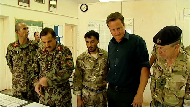 David Cameron visits Camp Bastion General views and close shots of Cameron chatting to Afghan army officers and looking at map of area and troop...