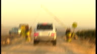 David Cameron visits refugee camp INT CAR **Car radio heard SOT** S POINT OF VIEW along road following other vehicles through crosspoint and along