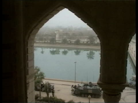 Day 19 Late news US Soliders on tanks parked outside Saddam's presidential palace TRACK TLMS US vehicles beneath arch of palace on banks of river...