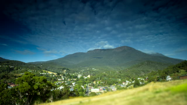 Day timelapse wide shot Mount Wellington White clouds pass over summit leaving shadows on forrested slopes Puffs of smoke from house chimney rise and...