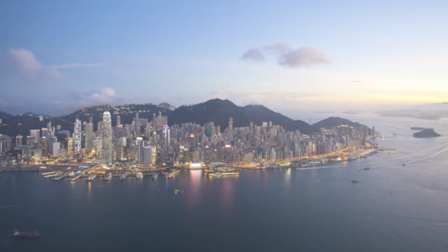 Day to Night, Aerial view over Hong Kong Island towards Victoria Peak showing the busy Victoria Harbour and Financial District of Central, Hong Kong, China, Time-lapse