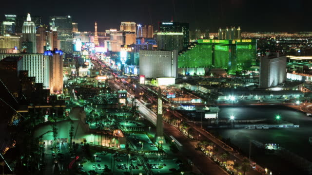 A day to night aerial view time lapse of the Las Vegas Strip, with the Luxor sphinx and obelisk in the foreground, with the MGM Grand, the Paris Las Vegas' Eiffel Tower, the New York, New York skyline, and several other south Strip casinos clearly visible