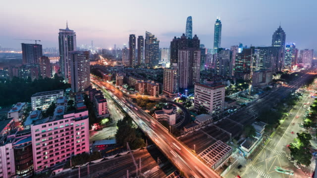day to night timelapse of shenzen skyline showing railway line and busy road