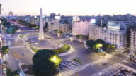 TL, WS, HA Day to night, traffic passes the obelisk / Obelisco de Buenos Aires / Buenos Aires, Argentina