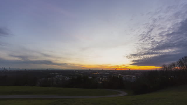 T/L ZOOM day to night transition overlooking Munich during a very colourful sunset