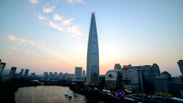 Day to night view of Lotte World Tower (The tallest building in Korea) and Seokchonhosu lake