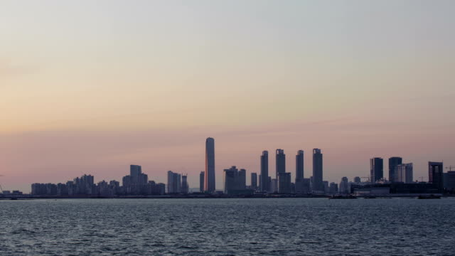 Day to night view of Northeast Asia Trade Tower (Second tallest building in Korea) and Songdo Island (International Business District) in distance