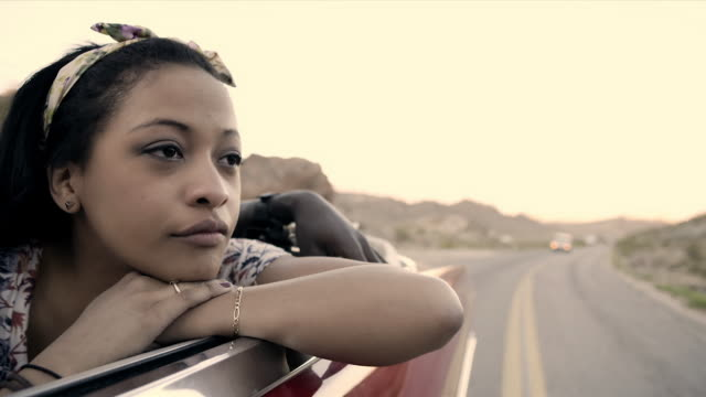 Daydreaming girl in classic convertible rests her head and watches the scenery pass by