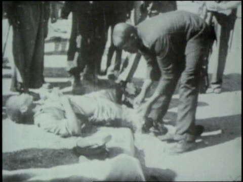 Dead bodies on ground badly wounded people are attended to and carried away white Afrikaner policemen standing guard The Sharpeville Massacre on...